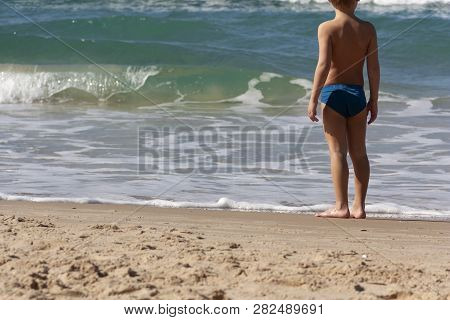 The Child Stands At The Edge Of The Sea