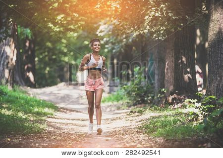 Young Lady Running. Woman Runner Running Through The Summer Park Road. Workout In A Park. Beautiful