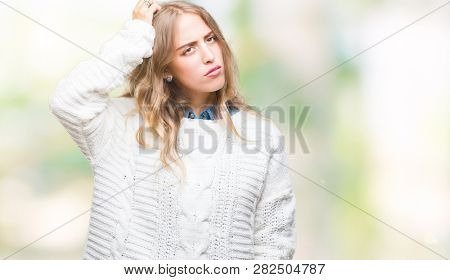 Beautiful young blonde woman wearing winter sweater over isolated background confuse and wonder about question. Uncertain with doubt, thinking with hand on head. Pensive concept.