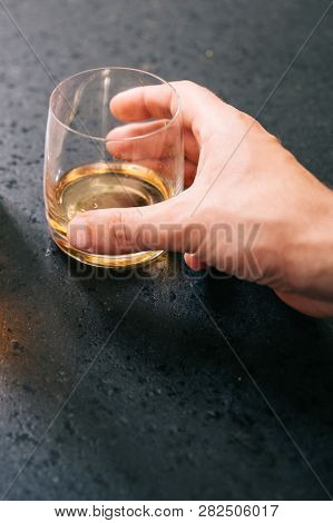 Male hand grasping a glass with whisky. poster