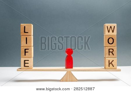 Red Human Figure Between The Words Life And Work On The Scales. Choice Between Life And Work. The Co