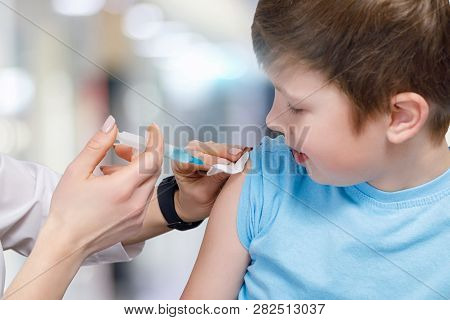 A Closeup Of A Teenage Child Receiving A Vaccine From A Pediatrician With A Syringe Fullfilled With