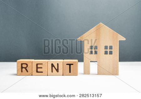 Wooden Figurine Houses And Cubes With The Word Rent. Search For Housing For Rent Or Property Rental.
