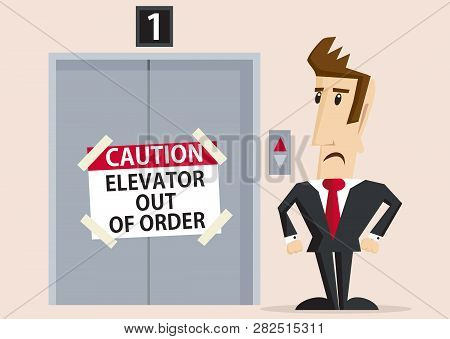 Unhappy Businessman Standing Next To Elevator Out Of Order With Caution Sign