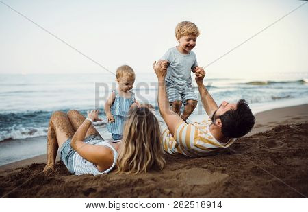 A Family With Two Toddler Children Lying On Sand Beach On Summer Holiday.
