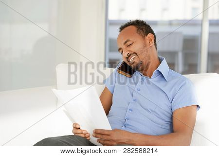 African Man Enjoying Good News In Writing. The Male Reads A Letter With Good News Sitting On The Cou
