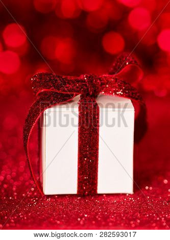 White Gift Box With Bright Red Ribbon On A Sparkling Background