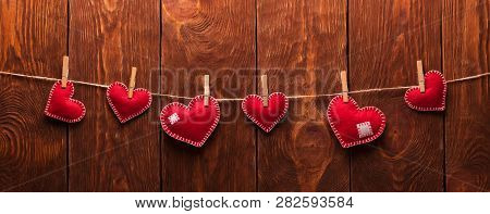 Happy Valentines Day. Handmade Felt Hearts Attached With Clothespins On A Rope On Wooden Background