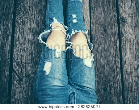 Ripped Jeans Female Feet. Fashion Womans Legs In Jeans And Shoes On Wooden Floor. Girl Is Sitting, W
