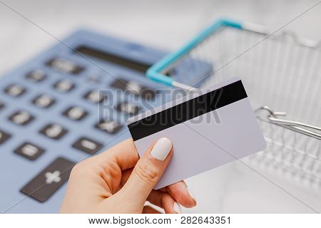 Woman's Hand Holding Payment Card In Front Of Huge Calculator And Shopping Basket