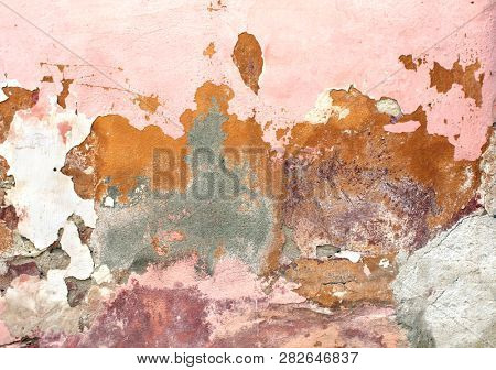 Grunge background with old stucco wall texture of pink color and cracked paint of red, beige and yellow color