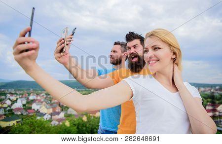 Todays Selfie. Pretty Woman And Men Holding Smartphones In Hands. People Enjoy Selfie Shooting On Na