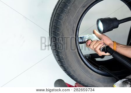 The Blure Hand Of Mechanic Holding A Drill And Drilled At  X Mark On Tire  During Repair The Leak Ho