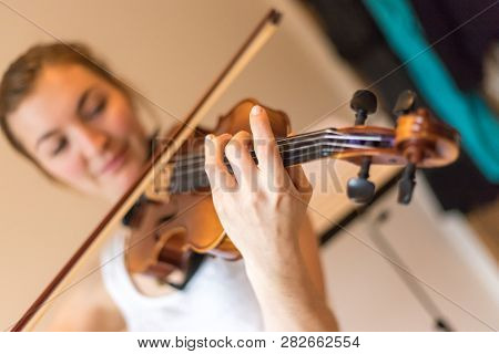 Young Girl Happily Plays On Her Violin