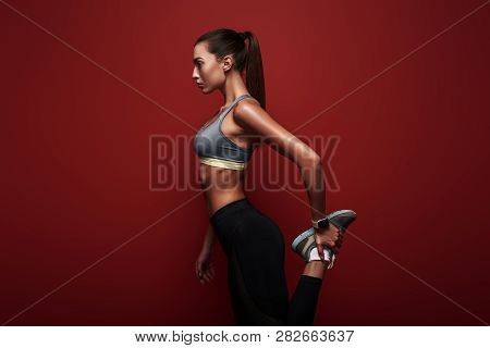 Full Of Energy. Sportswoman Standing Over Red Background, Stretching Her Body