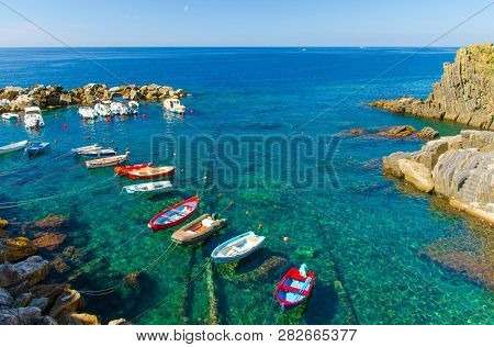 Fishing Colorful Boats On Transparent Water In Small Harbor Of Riomaggiore Village National Park Cin