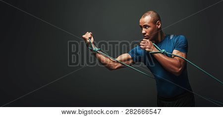 Go Sportsman Working Out With Resistance Band Over Dark Background