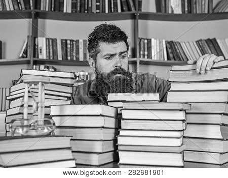 Bibliophile Concept. Teacher Or Student With Beard Sits At Table With Books, Defocused. Man On Hopef