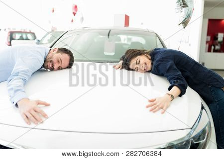 Content Hispanic Couple Embracing Their Newly Purchased Car In Automobile Salon