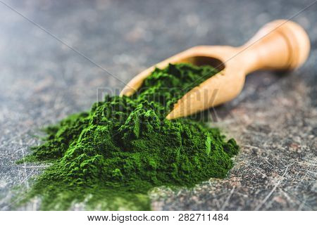 Green chlorella powder in wooden scoop.