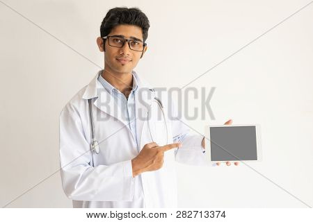 Young Indian doctor showing tablet computer. Smiling general practitioner pointing at digital tablet in his hand. Telemedicine concept poster
