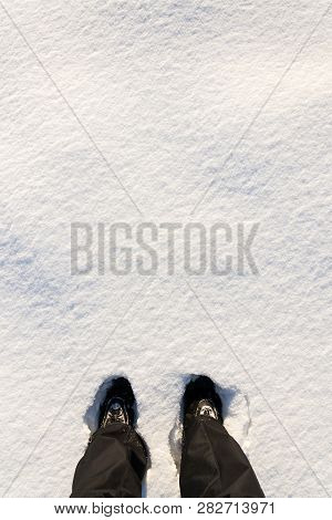 Top Flat Lay View Of Feet In Waterproof Winter Boots In Fresh Snow, Black Trousers, White Copy Space