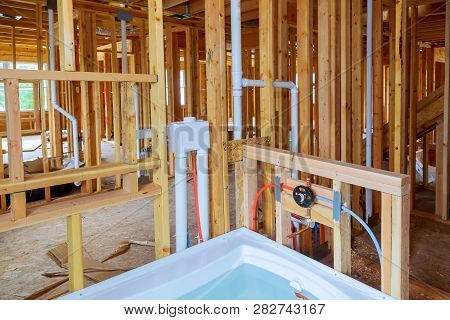 Interior Wall Framing With Piping And Bathroom Installed Plumbing Pipes And Exposed Beams.