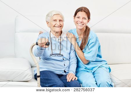 Smiling nursing woman and happy elderly woman with walker on the sofa