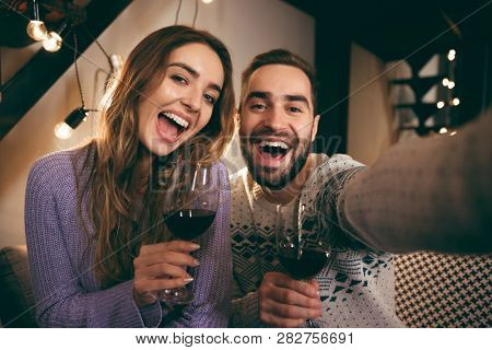 Beautiful happy young couple spending romantic evening together at home, drinking red wine, taking a selfie