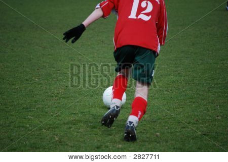 A soccer player is kicking the ball poster