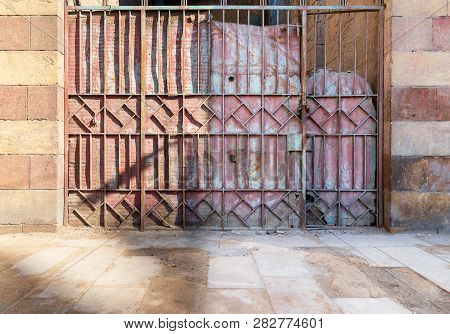 Background Of Old Weathered Grunge Antique Wrought Iron Gate With Geometrical Pattern Ornaments And