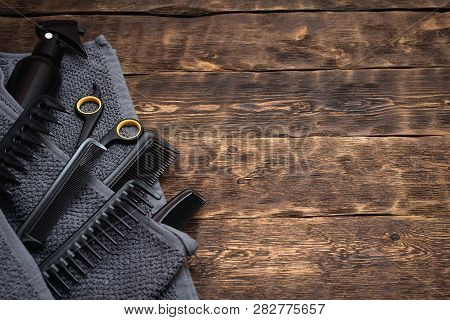 Hairdresser work table background with copy space. A various hairdressing tools such a hairbrushes, sprayer, towel and a scissors on a wooden board. poster