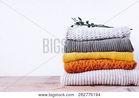 Pile Of Knitted Woolen Sweaters Autumn Colors On Wooden Table. Clothes With Different Knitting Patte