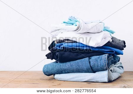 Stack Of Clothes On Table Indoor. Household Concept. Fresh Folded Cotton Jeans Clothing. Ironing, Do