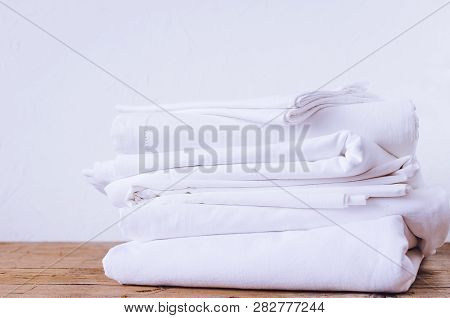 Stack Of White Linens On Table Indoor. Household Concept. Fresh Folded Bed Sheets. Ironing, Laundry,
