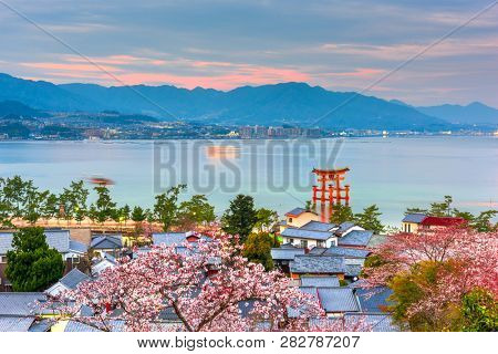 Miyajima Island, Hiroshima, Japan with temples on the Seto Inland Sea at dusk in the spring season.