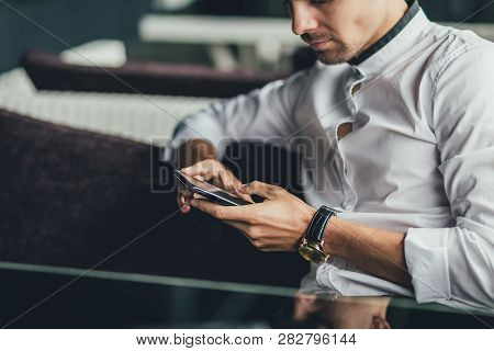 Man Using A Cell Phone On Cafe Terrace. Man Using Cellphone. Mans Hands With Cell Phone, Coffee. Man