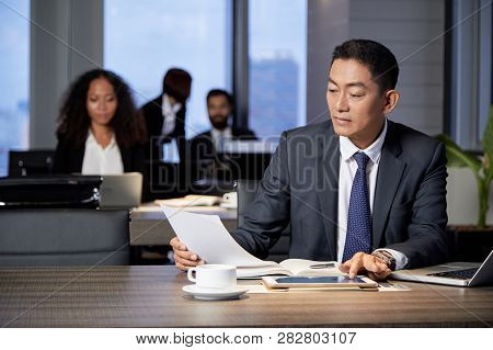 Serious Mature Vietnamese Entrepreneur Reading Contract At His Office Table
