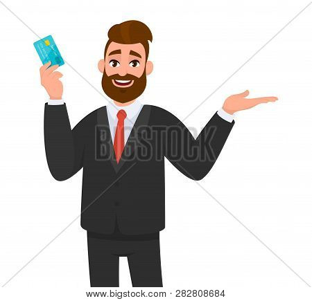 Smiling Business Man Showing Or Holding A Credit, Debit, Banking Card And Gestures Hand To Copy Spac