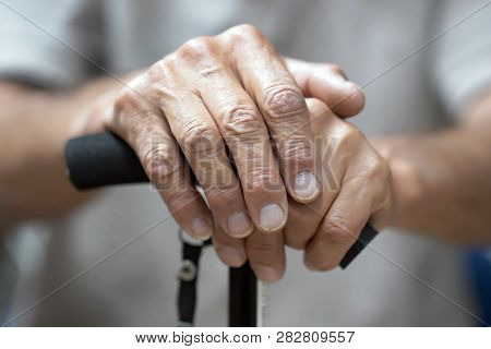 Senior Man Holding Cane. Close-up Of Old Man Hands On Walking Stick. Hand Of A Old Man Holding A Can