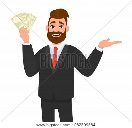 Smiling Young Businessman Showing Or Holding Cash, Money, Currency Notes, Dollars Or Banknotes In Ha