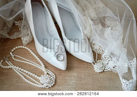 Luxury White Shoes On High Heels, Veil, Golden Wedding Rings And Bride Jewelry (pearls Necklace And