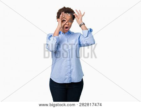 Young beautiful african american business woman over isolated background doing ok gesture shocked with surprised face, eye looking through fingers. Unbelieving expression.