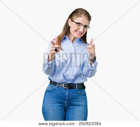 Beautiful middle age mature business woman wearing glasses over isolated background pointing fingers to camera with happy and funny face. Good energy and vibes.