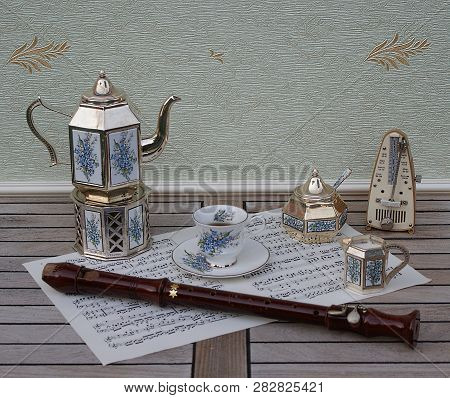 English Teacup And Saucer, Silver-plated Teapot On A Silver Stove, Cream Jug, Sugar Bowl And Sugar S