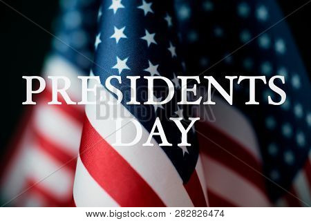 closeup of some american flags and the text presidents day against a dark background