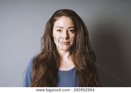 Happy Young Woman In Her 20s With Natural Make-up And Brunette Long Hair Smiling