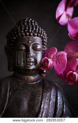 Buddha In Meditation With Orchid On Dark Background