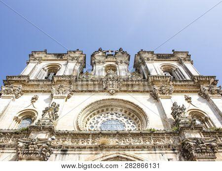 Low-angle Shot Of The Facade Of Alcobaca Monastery, Or Mosteiro De Santa Maria De Alcobaca, In Portu
