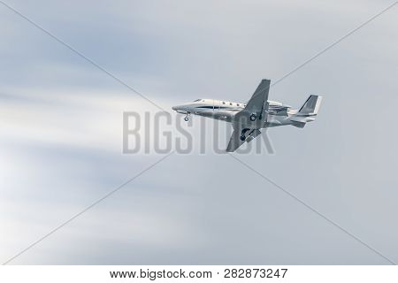Small commercial airplane flying at low altitude under a blue sky poster